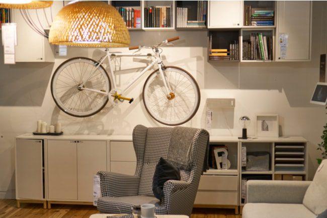 Vardagsrum visar compact living med cykeln hängandes på väggen ovan en skänk.