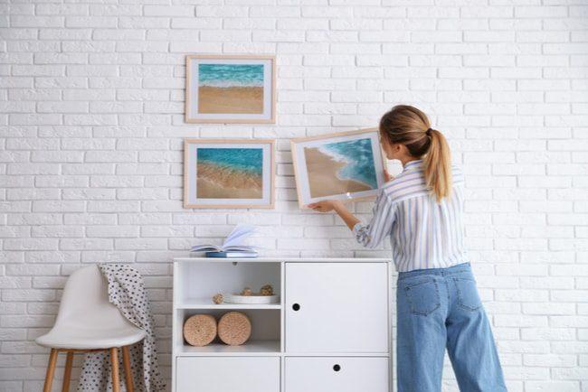 Ung tjej tar ner en av tre tavlor som hänger på en vit vägg