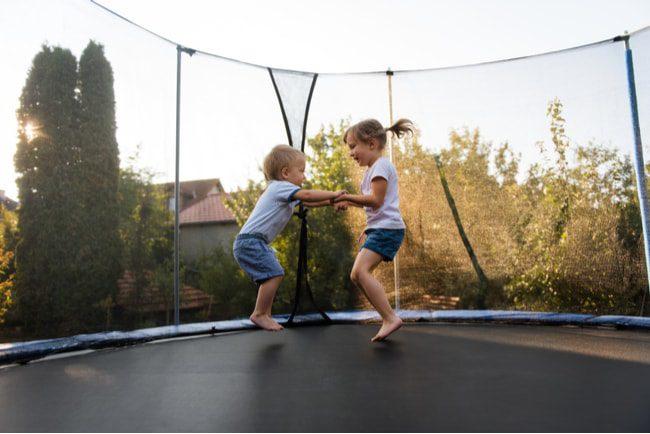 två barn hoppar på studsmatta hand i hand