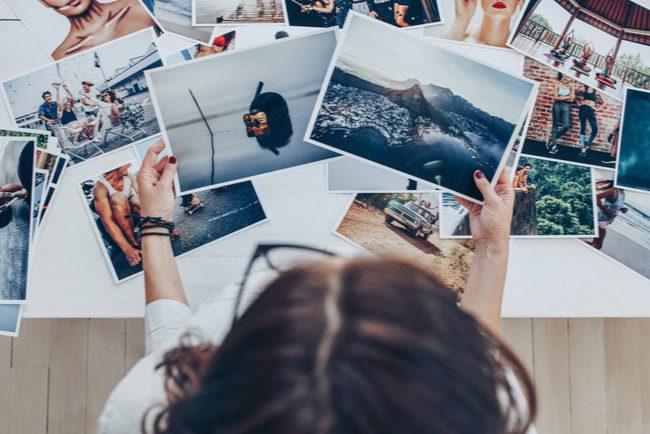 Kvinna med mörkt hår och glasögon sorterar fotografier.