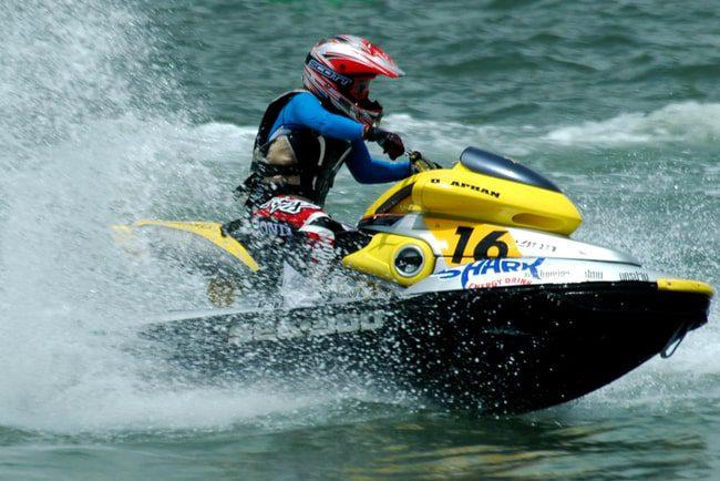 Kille i våtdräkt och hjälm kör en vattenskoter i hög fart.